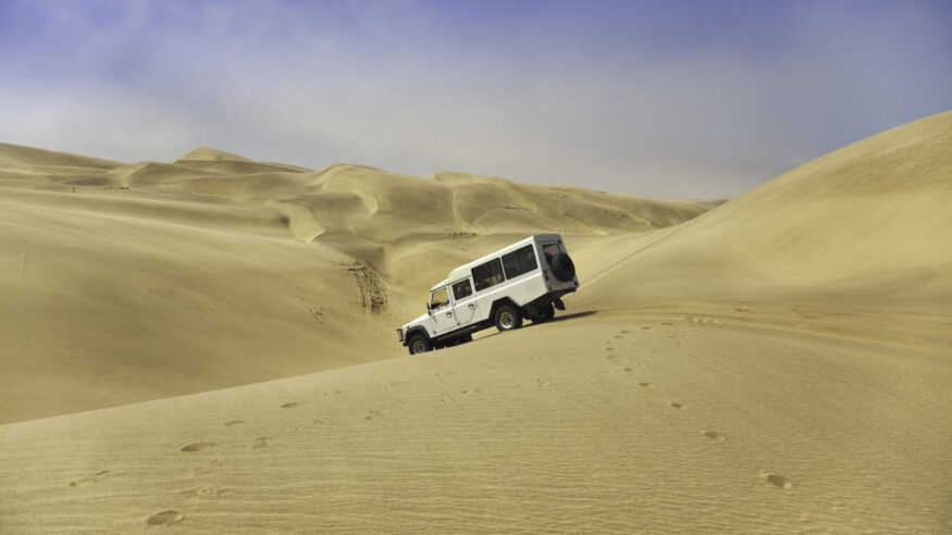 A four wheel drive vehicle descends the sand dunes between Walvis bay and Sandwich harbour.