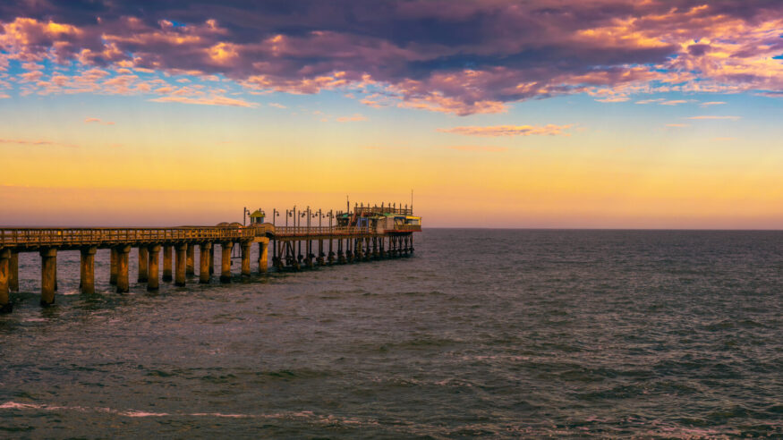 Colorful sunset over the old historic jetty in Swakopmund, Namibia. Swakopmund is situated in the Namib Desert and is the fourth largest population centre in Namibia.