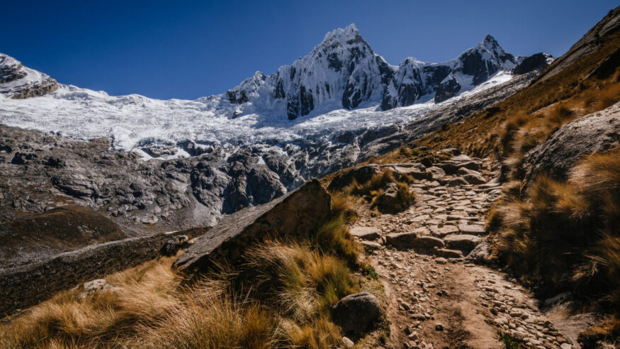 High snowy mountain of Taulliraju and path surrounded by grass in the foreground, in the quebrada santa cruz in peru
