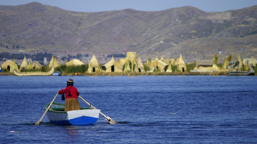 Woman rowing on Lake Titicaca near the floating islands