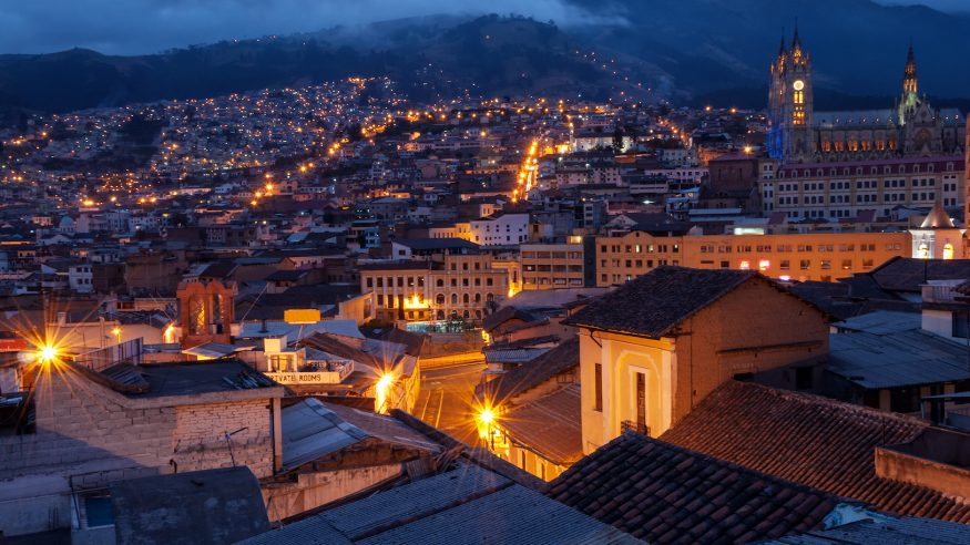 Quito, Ecuador old town and basilica at night with mountains in the background